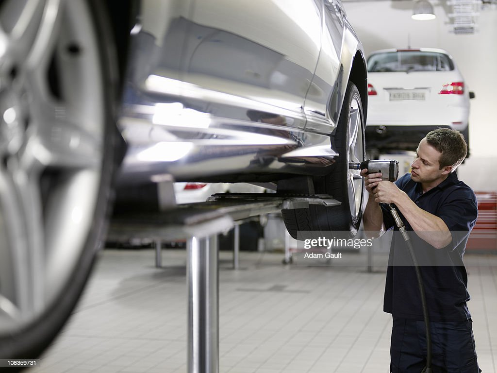 Mechanic working on car in auto repair shop : Stock Photo