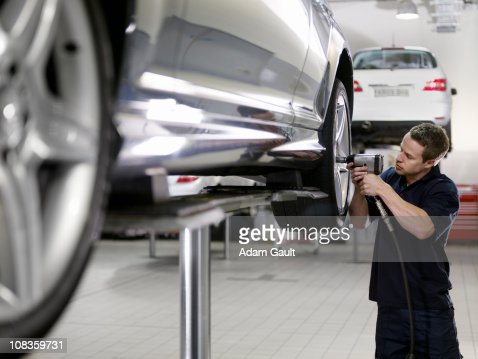 Mechanic working on car in auto repair shop : Foto de stock