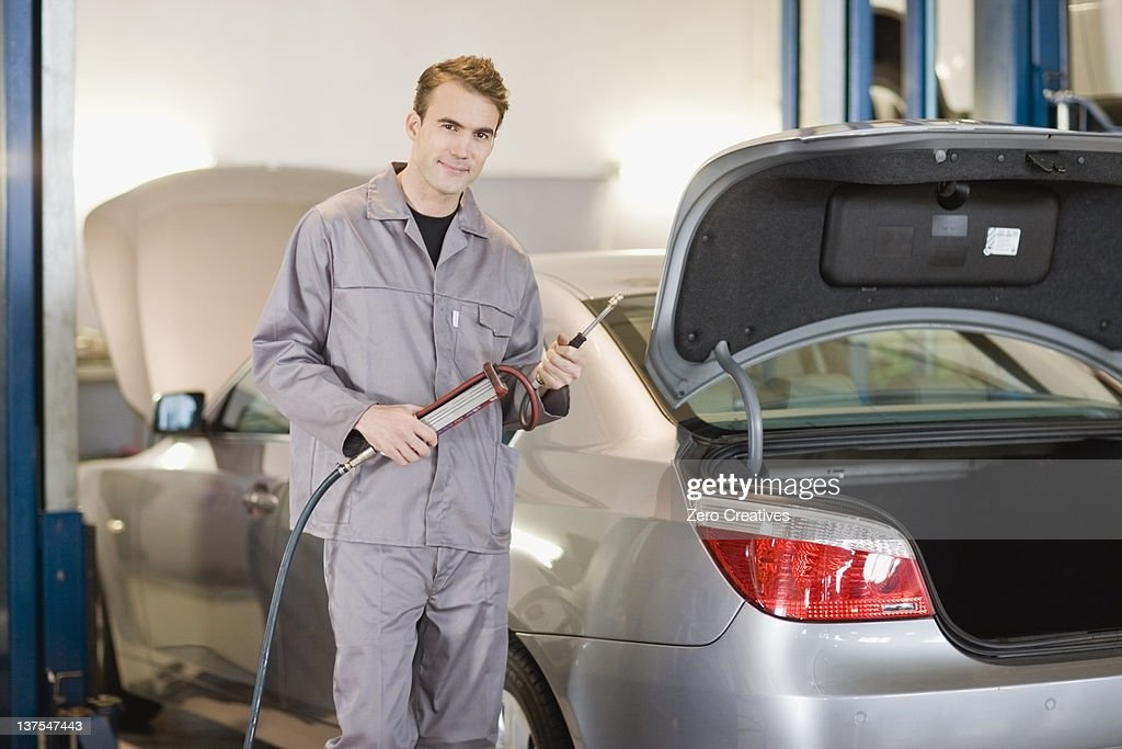 Mechanic working on car in garage : Stock Photo