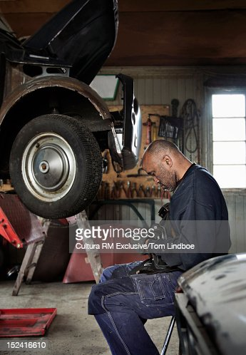 mechanic working on car in garage stock photo getty images. Black Bedroom Furniture Sets. Home Design Ideas