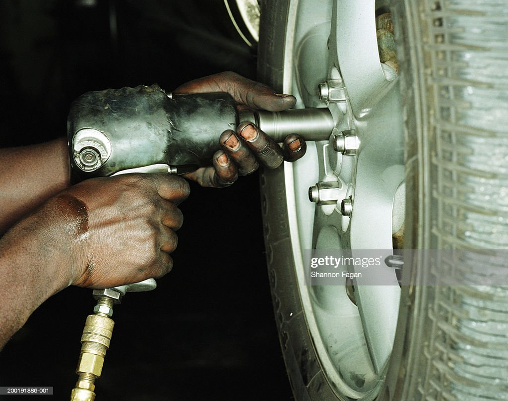 Mechanic working on car tire, side view, close-up : Stock Photo