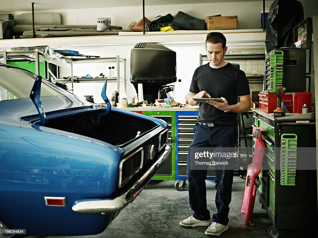 Mechanic working on digital tablet in garage : Stock Photo