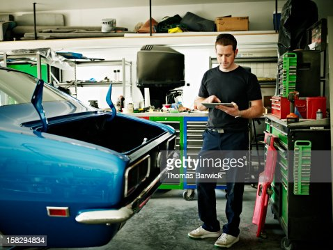 Mechanic working on digital tablet in garage : Photo