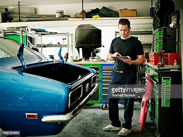 Mechanic working on digital tablet in garage