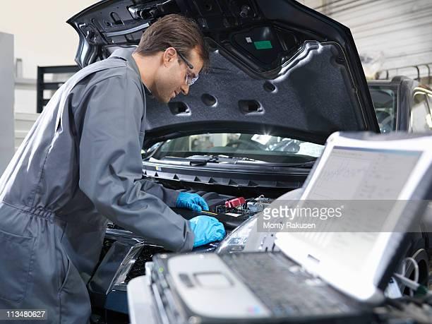 Mechanic working on engine analysis in car dealership workshop.  Laptop in foreground