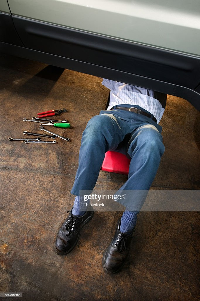 Mechanic working while lying on creeper under car