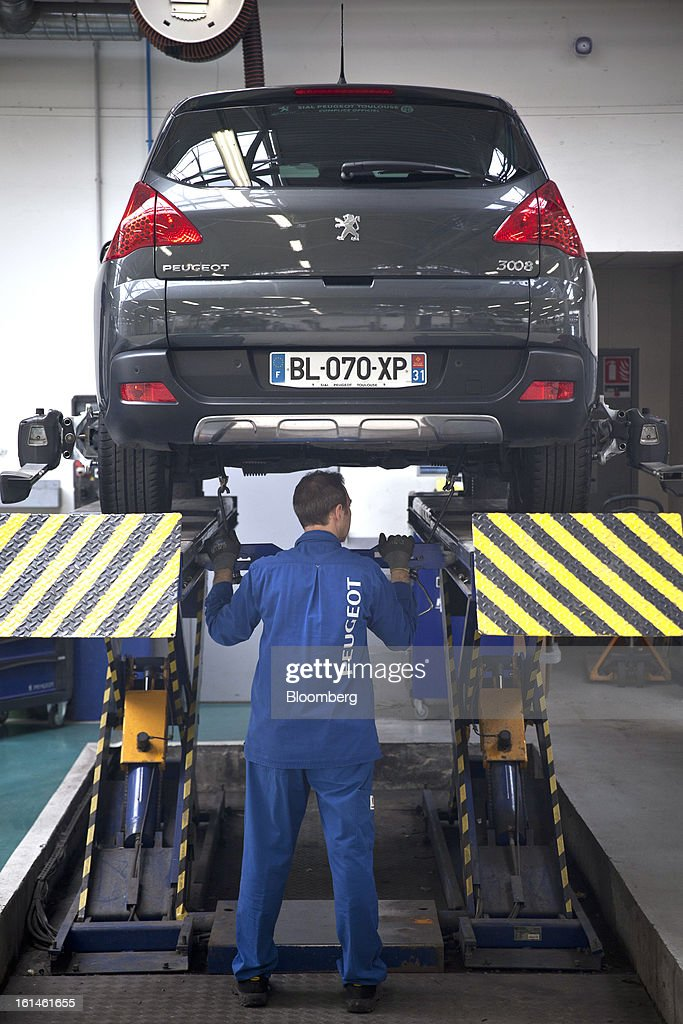 A mechanic works on a Peugeot 3008 automobile in a service bay at the Peugeot Sial Toulouse dealership in Toulouse, France, on Monday, Feb. 11, 2013. Europe's car market is forecast to drop to 12.3 million vehicles this year, 23 percent below the pre-crisis peak, IHS Automotive research company estimates. Photographer: Balint Porneczi/Bloomberg via Getty Images