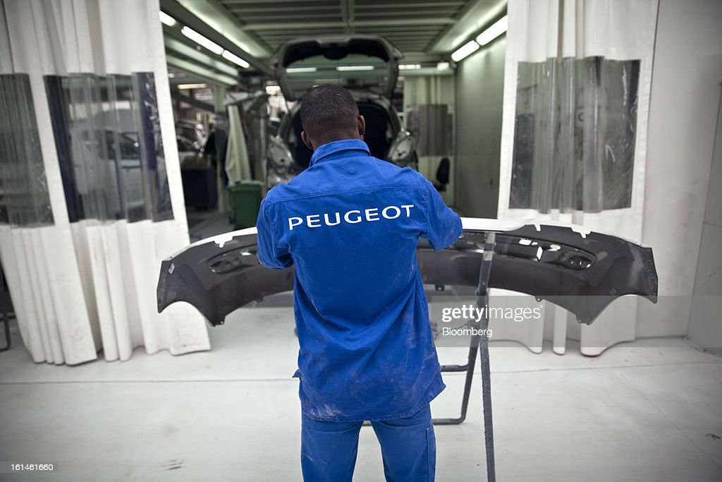 A mechanic works on an automobile bumper for a Peugeot vehicle inside the service area at the Peugeot Sial Toulouse dealership in Toulouse, France, on Monday, Feb. 11, 2013. Europe's car market is forecast to drop to 12.3 million vehicles this year, 23 percent below the pre-crisis peak, IHS Automotive research company estimates. Photographer: Balint Porneczi/Bloomberg via Getty Images