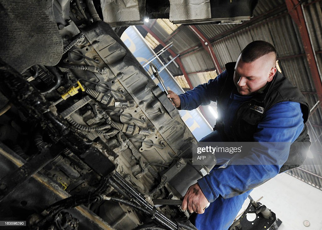 A mechanic works on an diesel engine of 410 horses power at the Transport Robineau workshop in Soulitre, western France, on March 12, 2013.