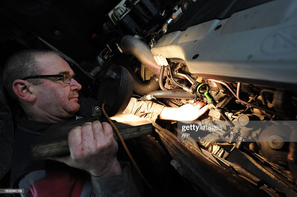 A mechanic works on an diesel engine of 440 horses power at the Transport Robineau workshop in Soulitre, western France, on March 12, 2013.