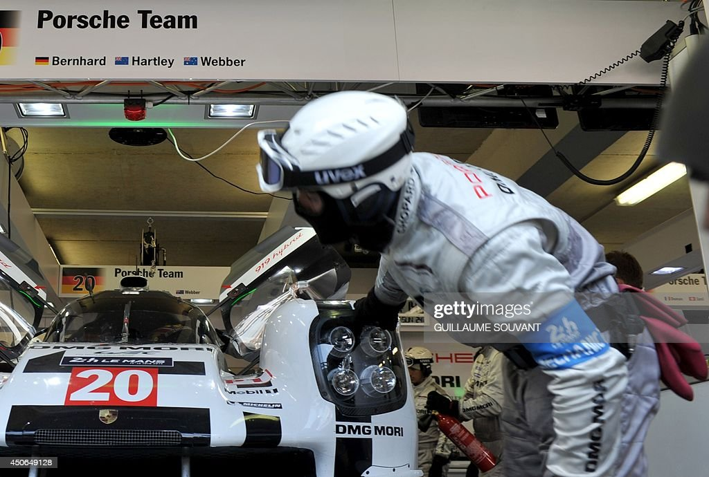 A mechanic works on Australian driver Mark Webber's Porsche 919 Hybrid N° 20 in the paddock during the 82nd edition of the Le Mans 24-hours (24 Heures du Mans) endurance race, on June 15, 2014 in Le Mans, western France. Austrialian former Formula One ace Mark Webber was leading the Le Mans 24 Hours endurance race with just three hours to go today after cashing in on the Audi team's misfortunes.