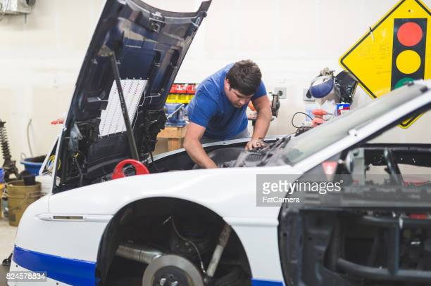 Mechanic works on car in his home garage