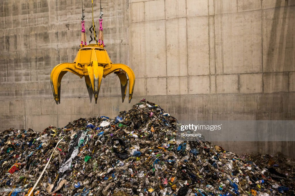 A mechanical claw collects trash in the bunker hall at the at the Renesciencewaste energy plant,operated by Dong Energy A/S, in Northwich, U.K., on Thursday, Oct. 5, 2017. The Renescience process starts with a giant claw that crunches into a mountain of trash and it ends with seven different types of materialfrom plastics to metals and biogas, that can be used to create electricity, recycled or sold on to a scrap yard. Nothing goes to landfill. Photographer: Matthew Lloyd/Bloomberg via Getty Images