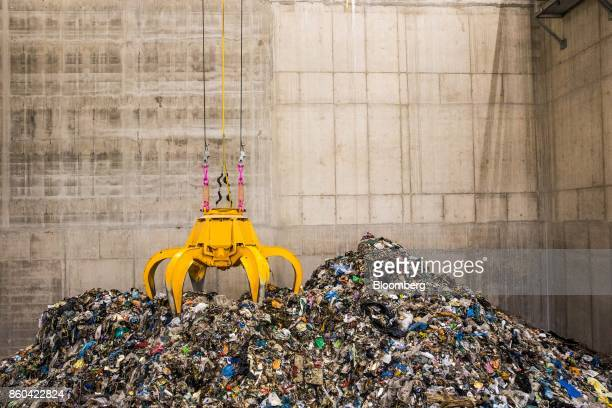 A mechanical claw collects trash in the bunker hall at the at the Renescience waste energy plant operated by Dong Energy A/S in Northwich UK on...