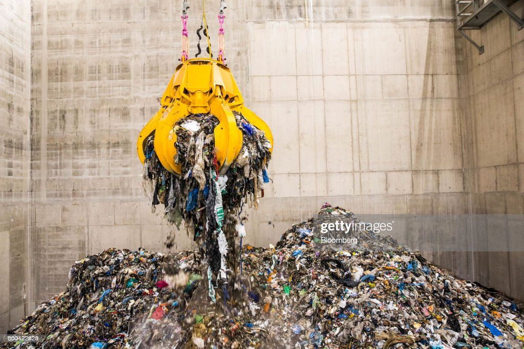 A mechanical claw collects trash in the bunker hall at the Renesciencewaste energy plant,operated by Dong Energy A/S, in Northwich, U.K., on Thursday, Oct. 5, 2017. The Renescience process starts with a giant claw that crunches into a mountain of trash and it ends with seven different types of materialfrom plastics to metals and biogas, that can be used to create electricity, recycled or sold on to a scrap yard. Nothing goes to landfill. Photographer: Matthew Lloyd/Bloomberg via Getty Images