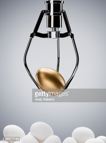 Mechanical claw lifting golden egg : Stock Photo