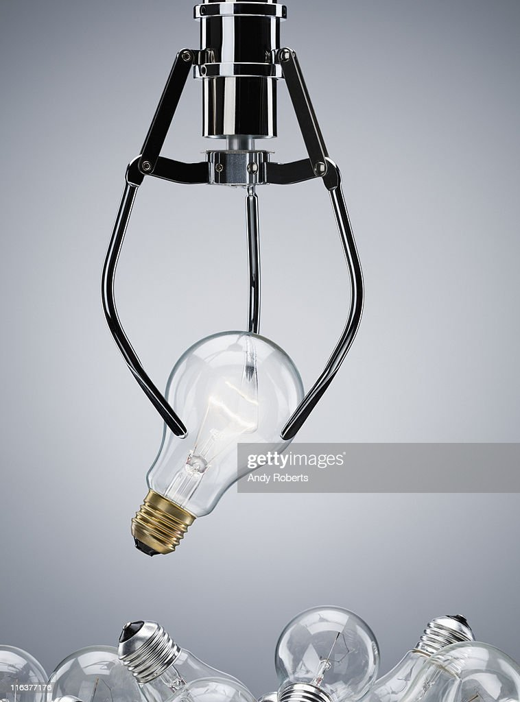Mechanical claw lifting light bulb : Stock Photo