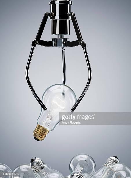 Mechanical claw lifting light bulb