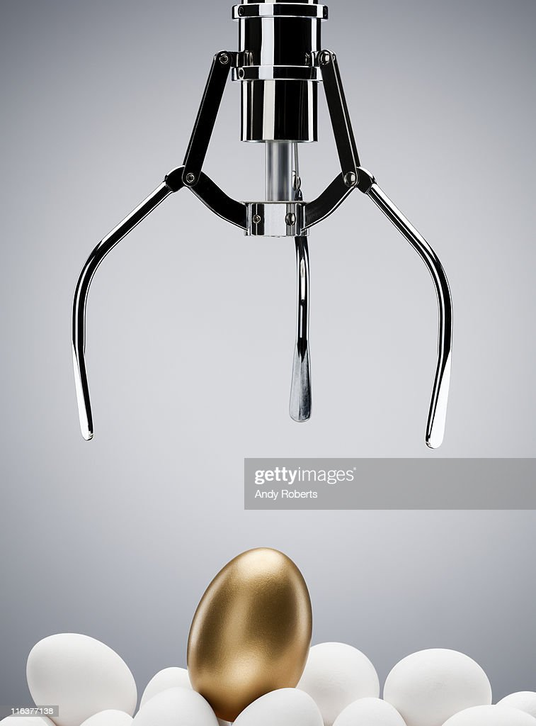Mechanical claw reaching for golden egg : Stock Photo