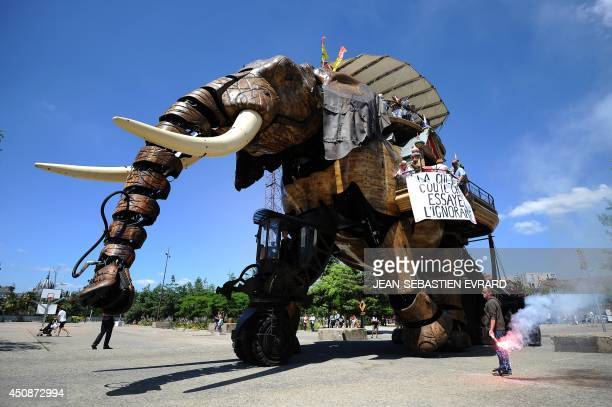 A mechanical elephant with a banner reading 'Culture is expensive Try ignorance' carries tourists as workers employed in the entertainment industry...