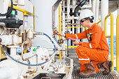 Mechanical engineer checking lube oil system of centrifugal pump and electric motor at offshore oil and gas central processing platform, Oil and gas exploration and production in the gulf of Thailand.