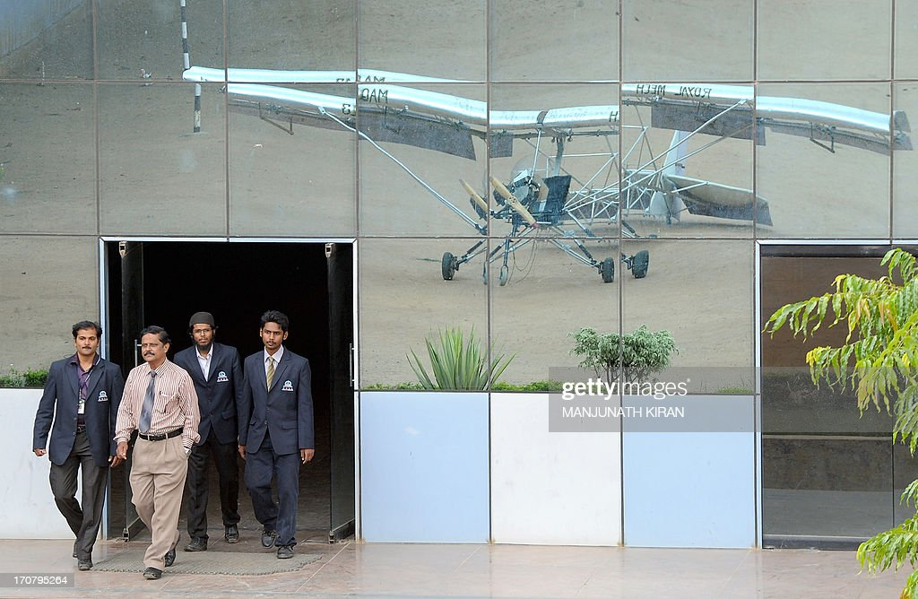 Mechanical Engineering student Mohammed Muzakkir Sharieff (L) and his project teammates walk out of a building showing the reflection of the aircraft they developed, the low cost manned microlight aircraft (MAQH 13), on the HKBK College of Engineering premises in Bangalore on June 18, 2013. The microlight aircraft, made to fly a payload of 200 kilograms, was designed and developed by a 4-member team as part of their ongoing final year project with a total cost of 45,000 rupees (USD 780). It is powered by a modified 150cc motorcycle engine with a wingspan of 24 feet (7.2 meters) and 17 feet (5.15 meters). Once completed the aircraft will undergo airworthiness tests after obtaining clearance and certification from the Director General for Civil Aviation (DGCA). AFP PHOTO/Manjunath KIRAN