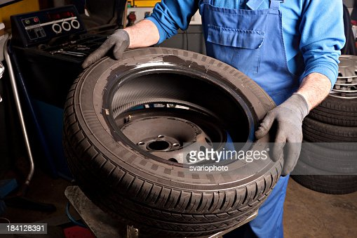 Mechanical repairs a tire in the garage