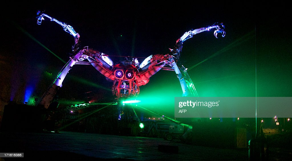 A mechanical spider moves around the site on the first night of the Glastonbury Festival of Contemporary Performing Arts near Glastonbury, southwest England late on June 26, 2013. The festival attracts 170,000 party-goers to the dairy farm in Somerset, and this year's tickets sold out within two hours of going on sale. The Rolling Stones will perform at the festival for the first time, headlining on Saturday night. AFP PHOTO/ANDREW COWIE