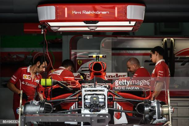 TOPSHOT Mechanics assemble Ferrari's Finland driver Kimi Raikkonen's car ahead of the Formula One Malaysia Grand Prix in Sepang on September 28 2017...