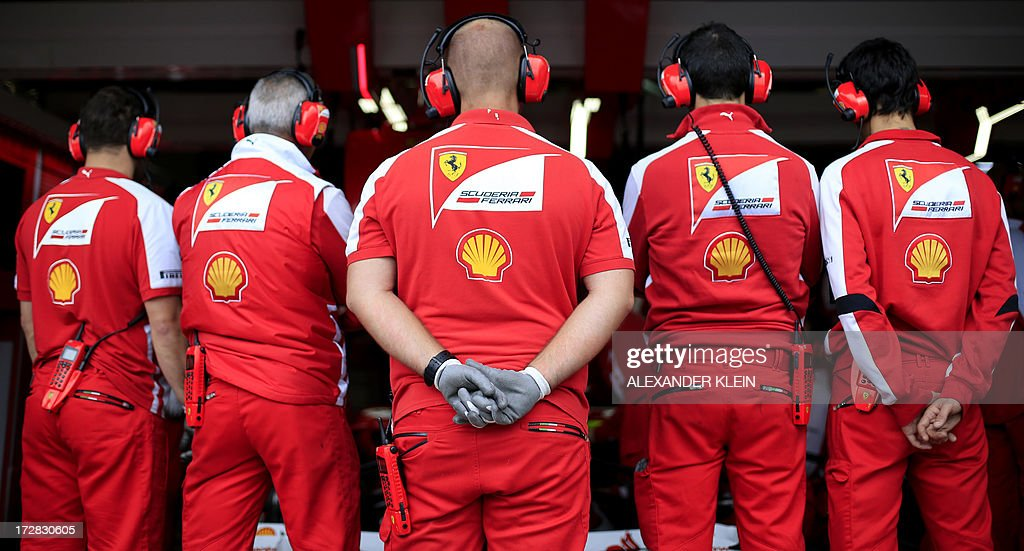Mechanics block visibility to Ferrari's Spanish driver Fernando Alonso's car in the pits during the first practice session at the Nurburgring racetrack on July 5, 2013 in Nurburg ahead of the German Formula One Grand Prix.