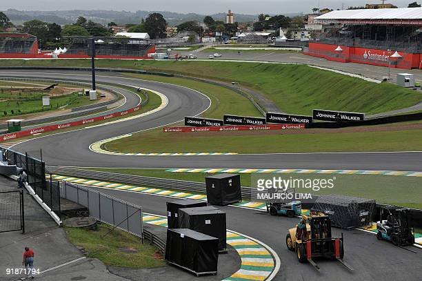 Mechanics carry their gear into the boxes area in the Senna S curve as part of preparations for the upcoming Brazilian Formula One GP at the...
