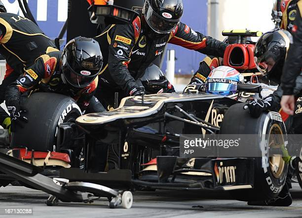 Mechanics change tires on the car of Lotus F1 Team's French driver Romain Grosjean in the pits at the Bahrain International Circuit in Manama on...