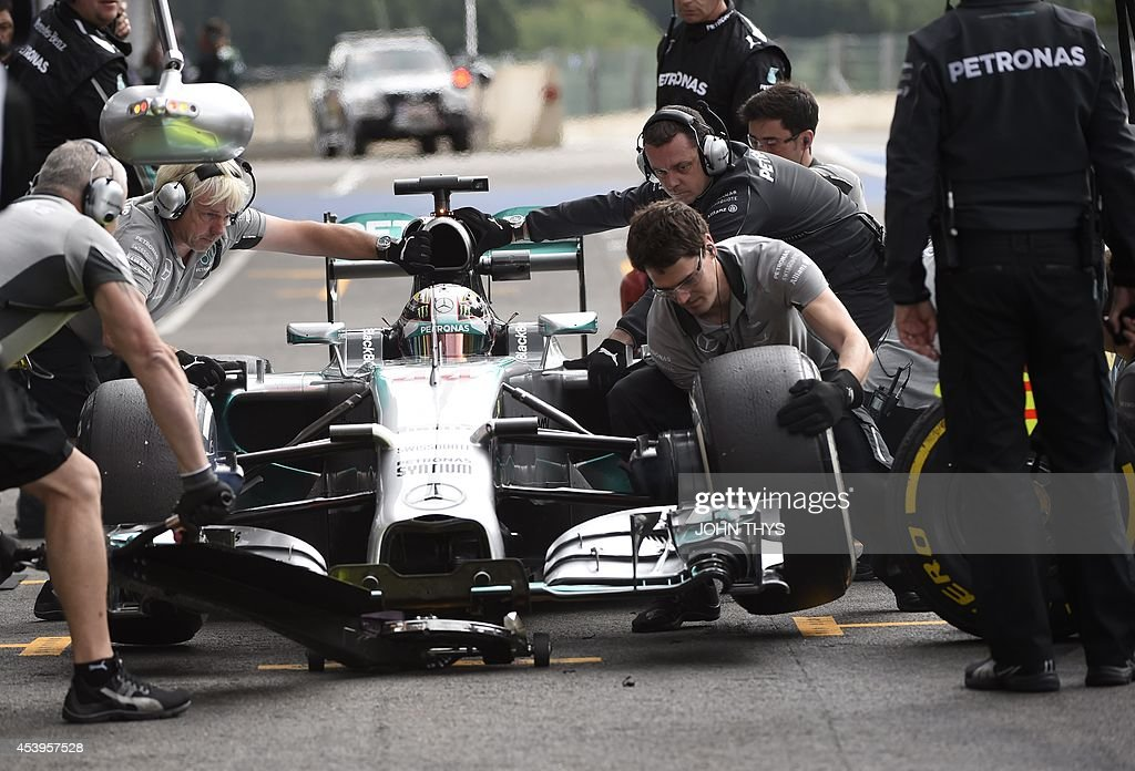 Mechanics change tires on the car of Mercedes-AMG's British driver Lewis Hamilton in the pits during the second practice session at the Spa-Francorchamps circuit in Spa on August 22, 2014 ahead of the Belgium Formula One Grand Prix.