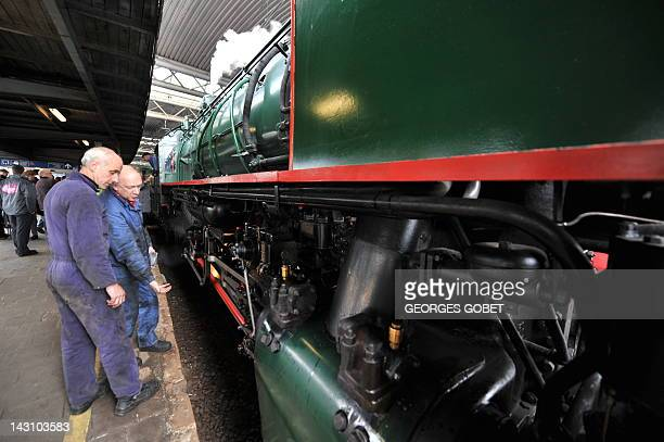 Mechanics check a Belgian 1940s locomotive on April 18 2012 at The Gare du Midi in Brussels on the occasion of the presentation of a cartoon of a...
