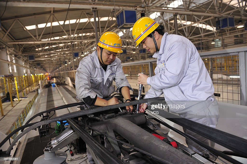 Mechanics check a high-speed train at Xi'an Electric Multiple Unit Maintenance Base on January 7, 2014 in Xi An, China. The 40-day 2014 Spring Festival travel rush will start on January 16 as more than 257 million passenger trips will be made on the railways.