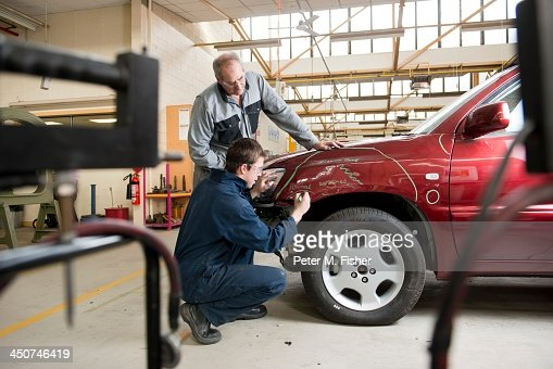 Mechanics checking damaged automobile