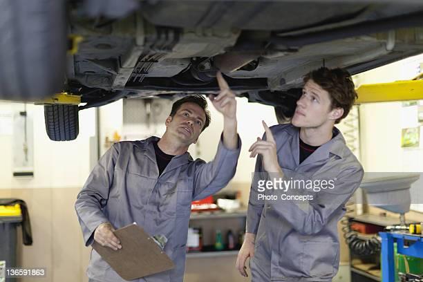 Mechanics examining underside of car