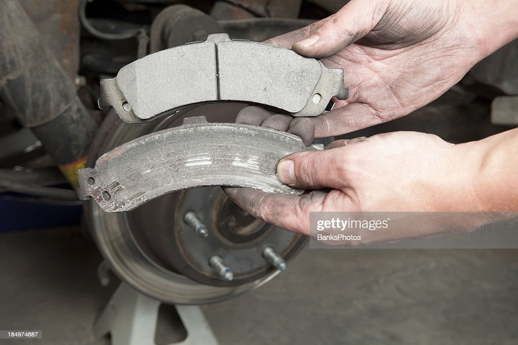 Car Break Pads Worn : Mechanics hands displaying worn and new brake pads stock