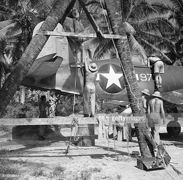 Mechanics hoist up the tail of a ChanceVought F4U Corsair before realigning its machine guns at a Marine advanced base in the South Pacific February...