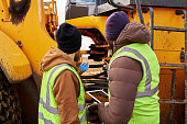 Back view portrait of two workers wearing reflective jackets, one of them African-American, discussing job on industrial site outdoors repairing big yellow truck