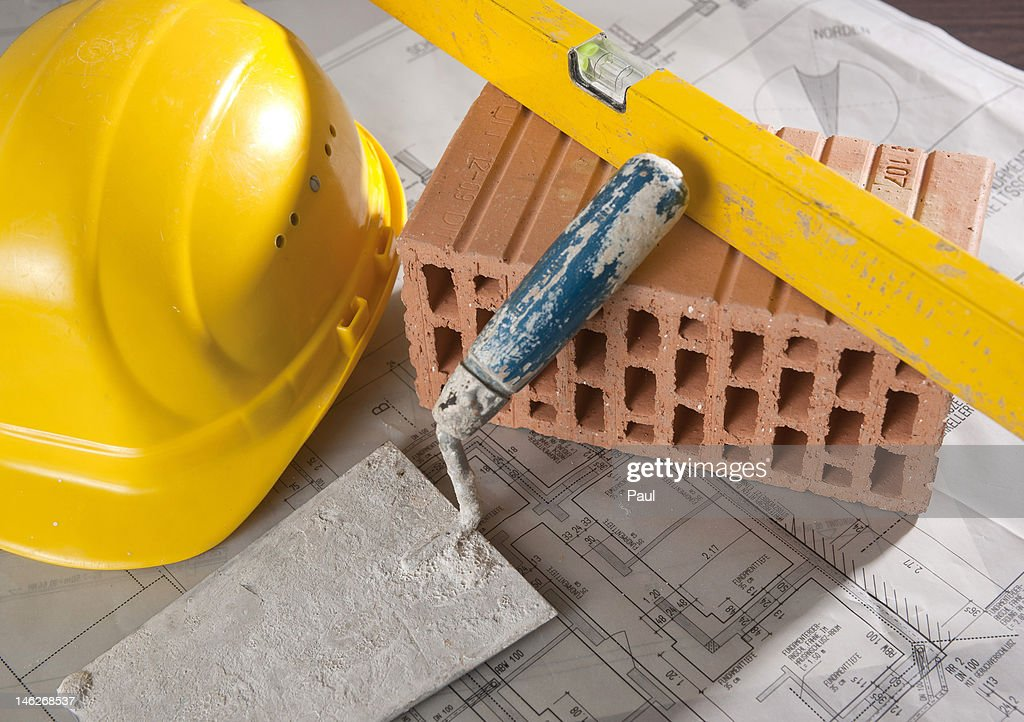 Mechanic's level, claybrick, trowel, hard hat and architectural drawing