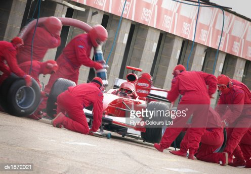 Mechanics Maintaining a Red Formula One Car at a Pit Stop : Stock Photo