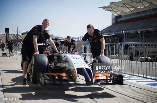 Mechanics move one of the cars for Sahara Force India F1 Team during the preview day for the 2014 Formula One United States Grand Prix at the Circuit...