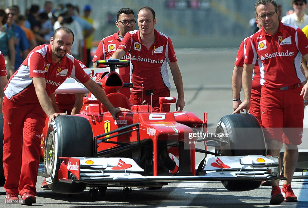 Mechanics of Ferrari Formula One team roll one of their cars for FIA's inpsection at Interlagos motorsport circuit in Sao Paulo on November 22, 2012 ahead of the Brazilian Grand Prix this weekend.