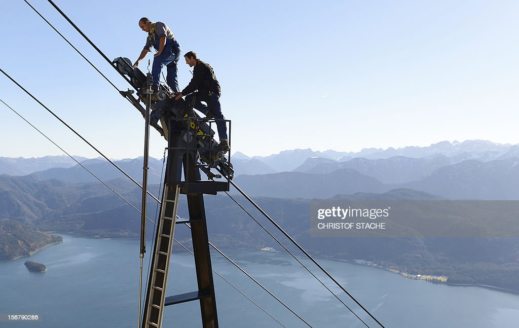 Mechanic's of the Herzogstand cable car inspect parts of the lift during the annual safety revision in front of the small village Walchensee, southern Germany on November 21, 2012. The technical revision of the Herzogstand cable car take part until December 21, 2012. The cable car starts in 800 meter at the small village Walchensee and finish at the Fahrenberg in 1.600 meter. Cable cars are prepared for the upcoming skiing season all over the Bavarian mountains. AFP PHOTO/CHRISTOF STACHE