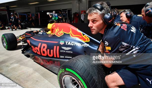 Mechanics push the car of Red Bull's Australian driver Daniel Ricciardo during the first practice session of the Formula One Russian Grand Prix at...