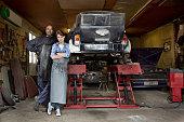 Mechanics standing with car in garage