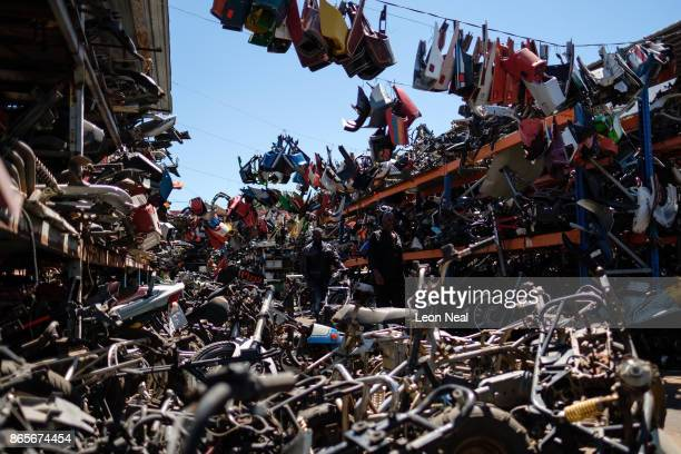 Mechanics walk among stacks of used engine components at 'The Bike Hospital' on October 18 2017 in Johannesburg South Africa The business has built...