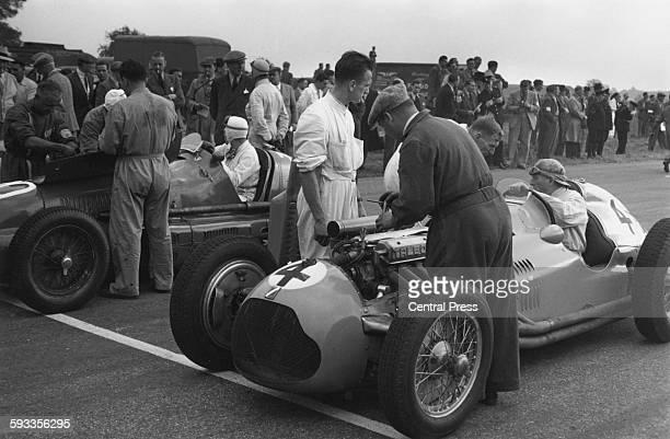 Mechanics work around Philippe Etancelin of France as he sits aboard the Ecurie Etancelin TalbotLago T26C before the start of the Royal Automobile...