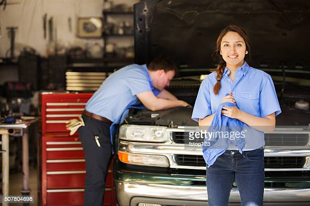 Mechanics work in an automobile repair shop. Man, woman working.